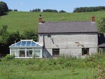Old grey farm, modern white conservatory. Stock Photos