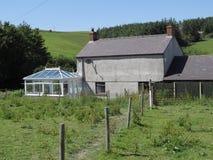 Old grey farm, modern white conservatory. Stock Image
