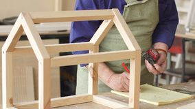 Old grey haired carpenter with moustache and beard measuring wooden doll house.