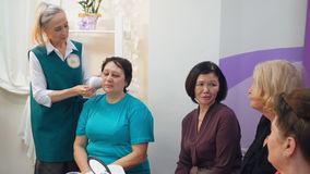 Old grey-haired nurse demonstrates hardware facial massage on client to group of elderly women. Senior grey-haired nurse woman demonstrates hardware facial stock video footage