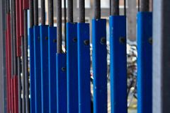Old Grey Metal Railing Blue And Red Plates. An old railing in front of a parking garage in Haarlem with some cool red and blue plates attached to it Royalty Free Stock Photo