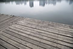 Old grey pier and reflection of buildings on river stock images