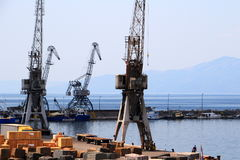 Old grey port cranes and small ships, harbor of Rijeka, Croatia. Old grey port cranes and small ships in the harbor in a sunny summer day in the city of Rijeka Royalty Free Stock Image