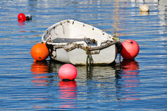 Old Grey Skiff. Small grey skiff with colourful floats/buoys  reflected in harbour waters Stock Images