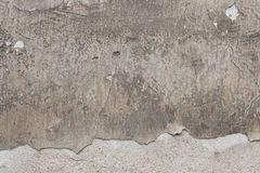 Old grey stucco wall with cracked plaster. Background texture Stock Images