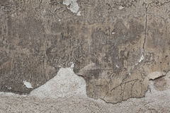 Old grey stucco wall with cracked plaster. Background texture Stock Photos