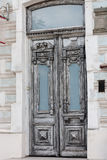 Old grey vintage double-leaf door. Olde grey vintage double-leaf door made of carved decorations painted in white wood framed with biege stones in Rostov-on-Don Stock Photo
