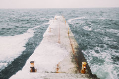 Old grey winter pier. Stormy sea on background.  royalty free stock images