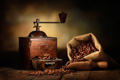 Old grinder with jute bag and coffee beans stock image