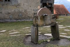 Old grinding machine. In the courtyard in front of the wall is an old stone grinding machine on the wooden bench Stock Images