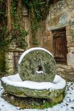 Old grinding wheel. Covered with snow in the winter Stock Image