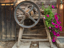 Old grindstone with crank and flowers Royalty Free Stock Images