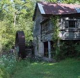Old Grist Mill. Abandoned Grist Mill, still has wheel, very old. Surrounded by trees and grass Royalty Free Stock Photography