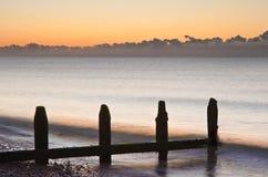 Old groynes on beach at sunrise Stock Photography