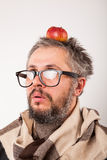 Old grumpy man with beard and big nerd glasses. With apple on head Stock Photography