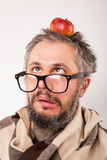 Old grumpy man with beard and big nerd glasses. Crazy looking grumpy old man with grey beard nerd big glasses with apple on head Royalty Free Stock Image