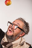 Old grumpy man with beard and big nerd glasses. Crazy looking surprised old man with grey beard nerd big glasses with apple on head Stock Image