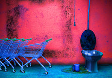 Old grunge bathroom. Vintage room interior, old floor, wall, toilet and shopping carts Stock Photo