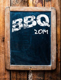 Old grunge BBQ advertising sign. On an old school slate board with a distressed wooden frame and copyspace for your text mounted on wooden boards royalty free stock image