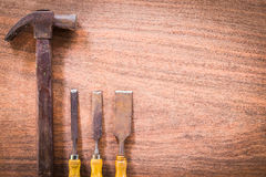 Old & grunge hammer and chisel for carpentry on wood floor Royalty Free Stock Photo