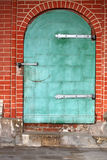 Old grunge looking green steel door with brick wall Royalty Free Stock Photos