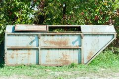 Old grunge metal dumpster can for garbage with rusty spots on the green grass surface in the city park. Old grunge metal dumpster can for garbage with rusty Royalty Free Stock Photos