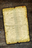 Old grunge paper on brown wooden surface Royalty Free Stock Photos