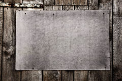 Old grunge plywood board on a wooden wall Royalty Free Stock Photography