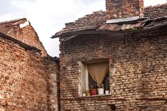 Old grunge weathered house brick wall backside facade. Old grunge poor weathered house brick wall backside facade with window and ruinous roof with vintage tiles royalty free stock photography