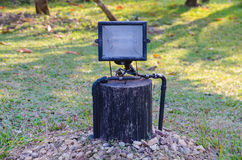 Old grunge rust spot led light on wood with green grass background. Royalty Free Stock Images