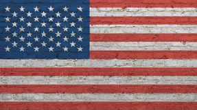 Old vintage American US flag over brick wall. Old grunge vintage American US national flag graffiti over background of white brick wall Stock Photo