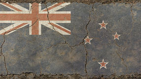 Old grunge vintage faded flag of New Zealand. Old grunge vintage dirty faded shabby distressed New Zealand national flag background on broken concrete wall with royalty free stock photos