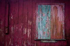 Old grunge and weathered home facade with green window and red wall planks texture background royalty free stock photos