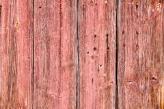 Old grunge and weathered light red wooden wall planks texture. With rusted nails and holes due to exposure to the elements outdoors Stock Photos