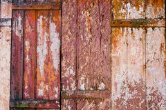 Old grunge and weathered red, yellow and white wooden wall planks texture background stock images