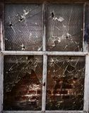 Old grunge window. Old broken window with bullet holes and broken glass Stock Image