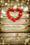 Old grunge wooden board with light bulb border, strawberry in the shape of a heart. Royalty Free Stock Photos
