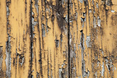 Old grunge worn wooden board with cracked and peeled brown yellow paint. Stock Photo