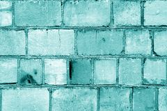 Old grungy brick wall surface in cyan color. Abstract architectural background and texture for design blue green cement wallpaper grunge concrete block pattern stock image