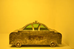 Old grungy car miniature against yellow bright background Stock Photography
