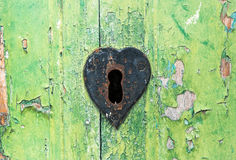 Old grungy green door and rusted lock. Old grungy green wooden door with peeling paint and rusted lock with a heart shaped escutcheon around the key hole Stock Photography