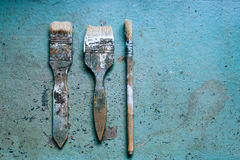 Old grungy paint brushes. Tools on the metal blue table stock photography