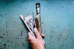 Old grungy paint brushes. Tools on the metal blue table royalty free stock photography