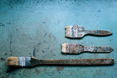 Old grungy paint brushes. Tools on the metal blue table stock images