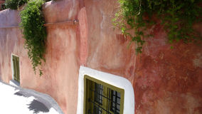 Old grungy pink wall, and decorative Windows on it in Oia Royalty Free Stock Image