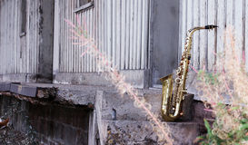 Old grungy saxophone. With old retro background Stock Photos