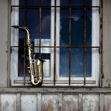 Old grungy saxophone. With old retro background Royalty Free Stock Photos