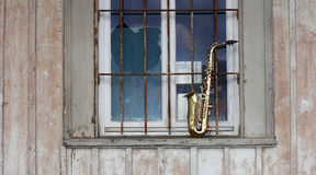 Old grungy saxophone. With old retro background Stock Photography