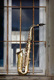Old grungy saxophone. With old retro background Royalty Free Stock Photography