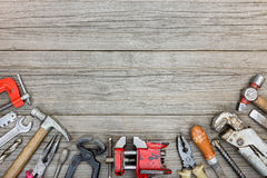 Old grungy tool set including hammers, drills, pliers, wrenches. And clamps on gray wooden boards background Royalty Free Stock Photo